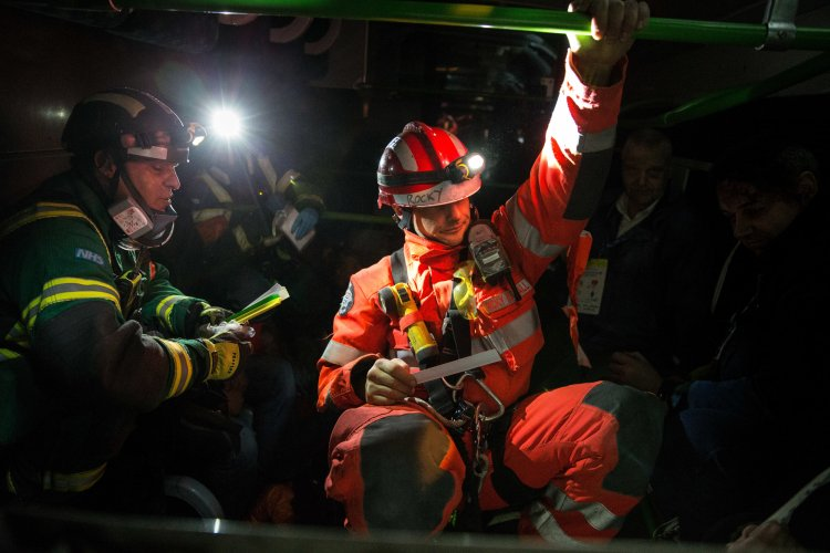 Emergency service workers inside a destroyed London Underground train carriage treat 'survivors'