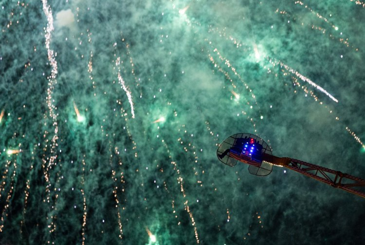 People riding on a fairground ride as fireworks go off to close the Isle of Wight Festival
