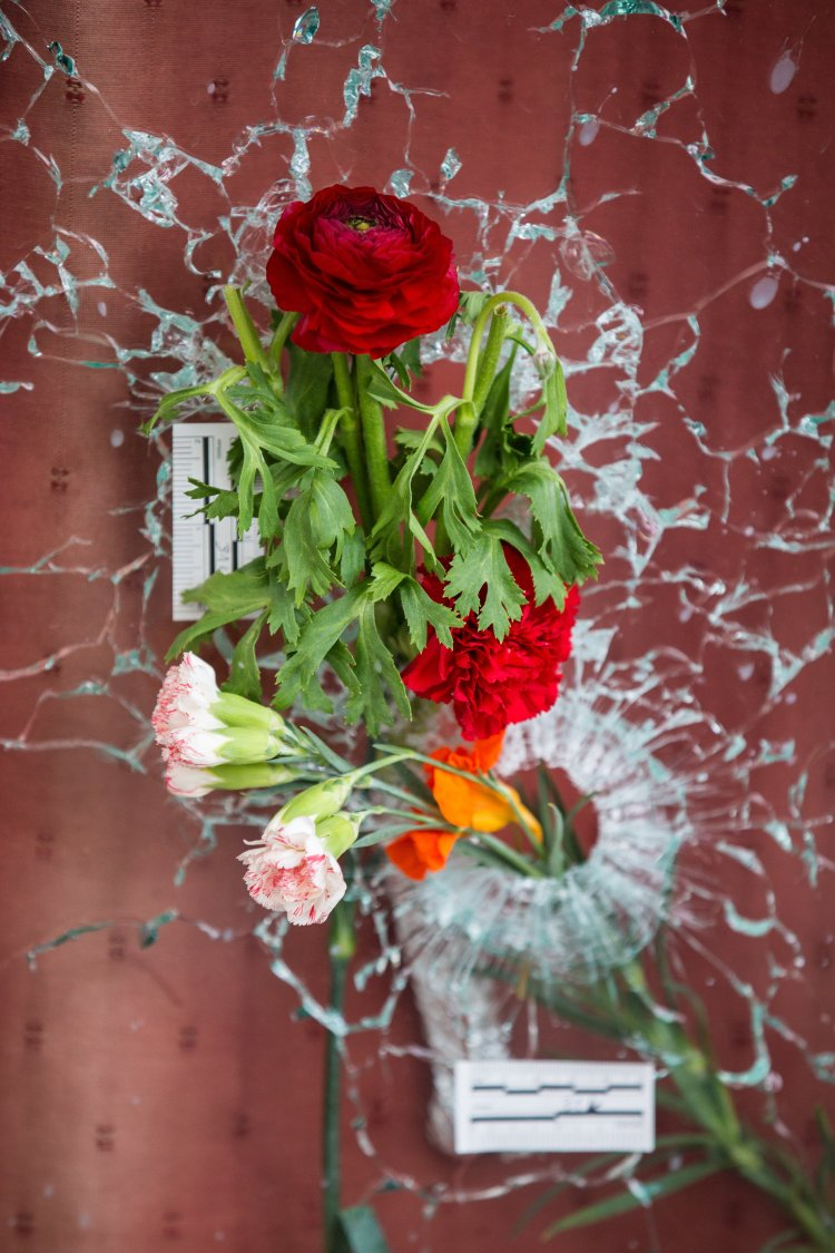 Flowers placed through bullet holes in the window of Le Carillon