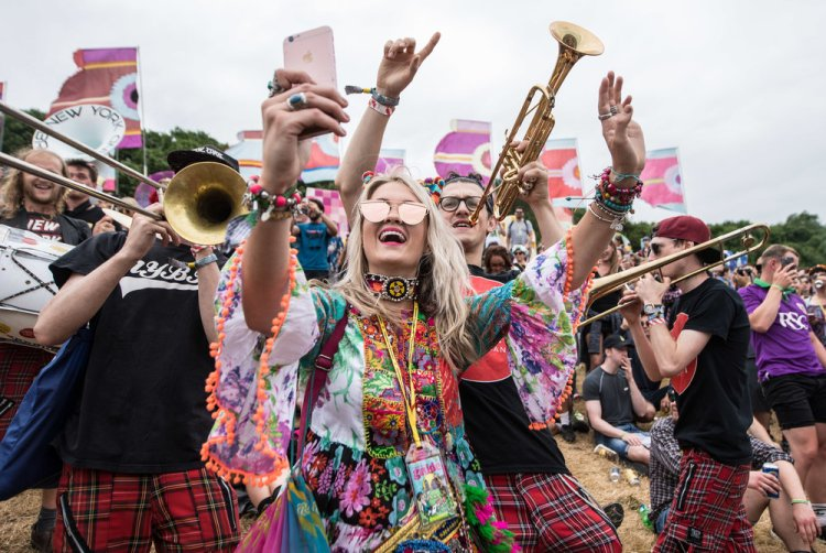 A festival goer dancing to a brass in the 'Above the Park' area of Glastonbury Festival