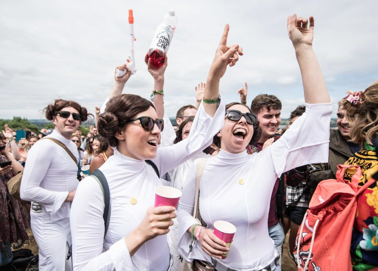 Festival goers dressed as Princess Leia from Star Wars dancing to a brass band