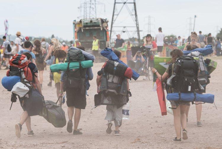 Festival goers walking on a dusty path