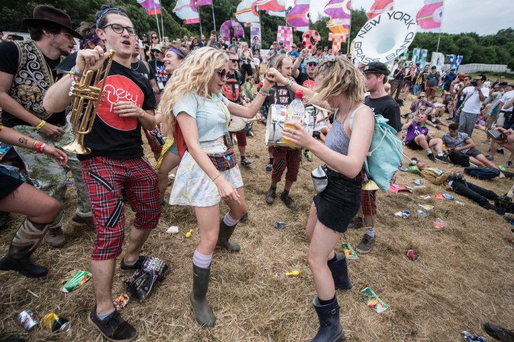 Festival goers dancing to a brass in the 'Above the Park' area of Glastonbury Festival
