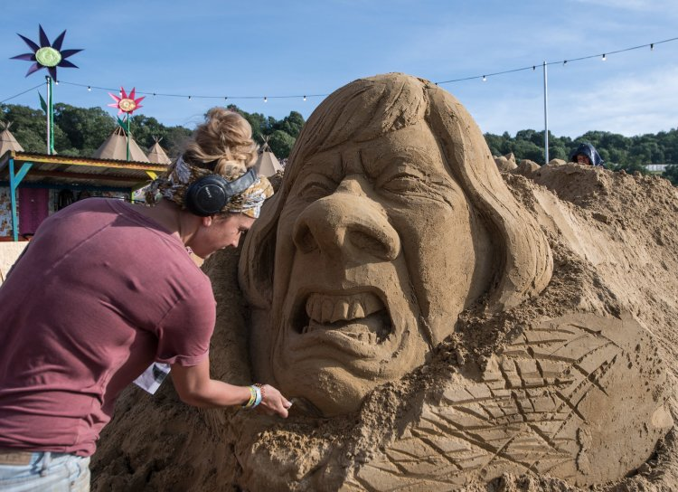 A sand artist making a sculpture of Theresa May