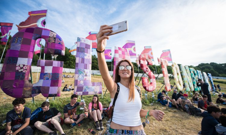A festival goer taking a selfie at the Glastonbury sign