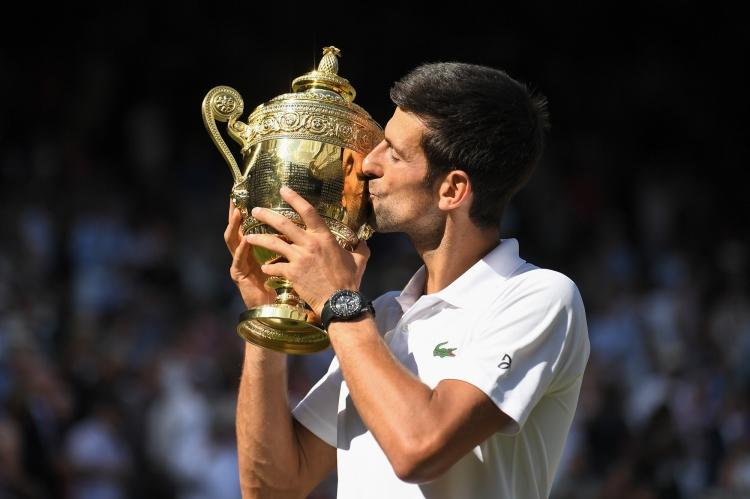 Novak Djokovic celebrates victory with the trophy in the Gentlemen's Singles final